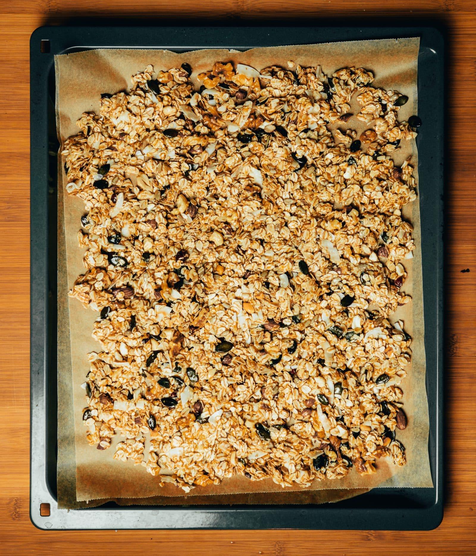 Verteile die Masse gleichmäßig auf einem mit Backpapier ausgelegten Backblech und schiebe es in die Mitte des Ofens.